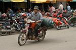 man transporting gas containers on a bike