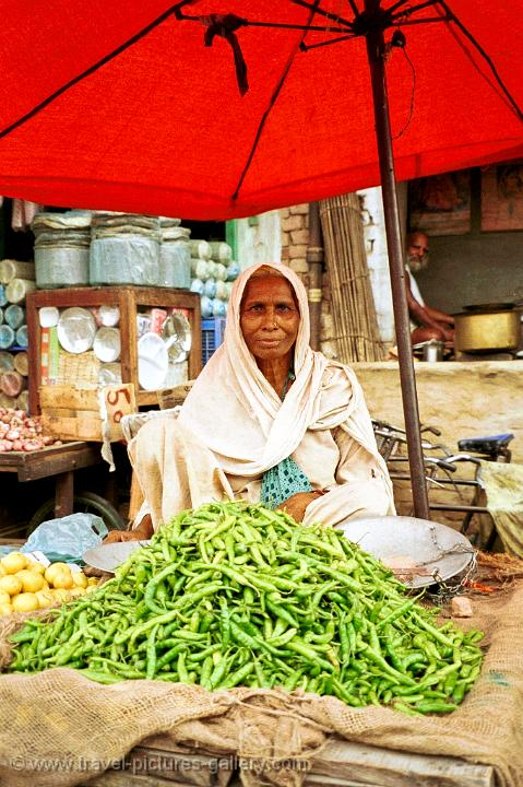 lady selling green peppers at a market
