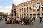 group of tourists posing with the Colosseum