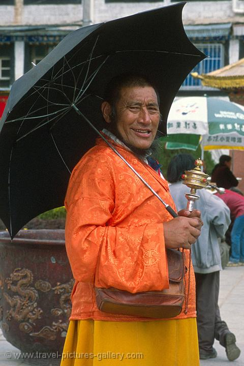 a pilgrim with a prayer wheel and umbrella